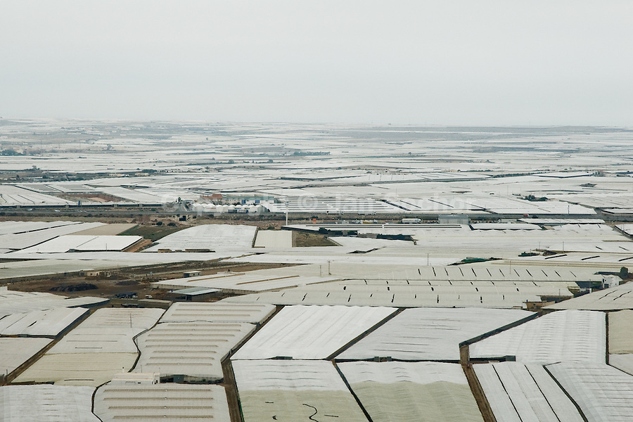 The plastic sea of greenhouses seen from the top of a skyscraper built in El Ejido, Spain, 23 May 2007. El Ejido, a dry region on the coast of Andalusia, has changed during the last decades into the centre of vegetable production not only for the Spanish market. A half of Europe is supplied by tomatoes, peppers and melons from El Ejido. This economic miracle is from a major part based on a cheap labor force of illegal immigrants from Maghreb and Subsaharian Africa. Tens of thousands of workers keep the plastic sea of greenhouses running for the minimum wage of 30 Euros a day.