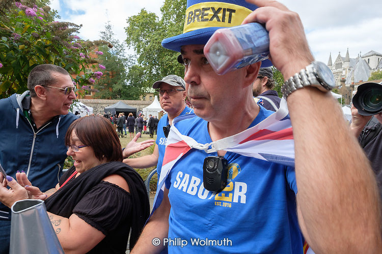 Steve Bray ('Mr Stop Brexit') retrieves his hat after it was seized by far-right Brexiters.  Campaigners for and against Brexit demonstrate outside Parliament on the day MPs voted to take control of the order paper, Westminster, London.
