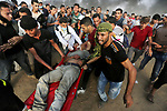 A wounded Palestinian protester is evacuated during clashes with Israeli troops in tents protest where Palestinians demand the right to return to their homeland at the Israel-Gaza border, in Khan Younis in the southern Gaza Strip on October 19, 2018. Photo by Ashraf Amra