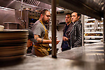 Brothers Mark (left) and Jonnie Houston at their restaurant and bar Butchers and Barbers speak to Chef Luke Reyes in the kitchen in Los Angeles, California January 3, 2014.