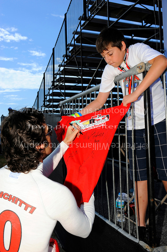 Dario Franchitti (#10) signs an autograph for a fan.