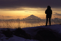 A sightseer watches the sun set behind Mount Redoubt from a popular vantage point on the Cook Inlet beach in Kenai, Alaska, at the mouth of the Kenai River. The 10,197-foot active volcano is the most dominant landmark on the Kenai horizon.