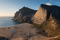 Steep granite face of Helvetestind rises over Bunes beach, Moskenesøy, Lofoten Islands, Norway