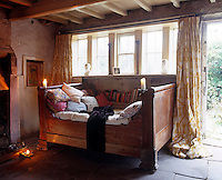 Piled with scatter cushions, the massive antique daybed next to the living room fireplace makes a beguiling retreat
