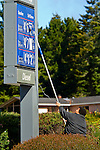 Gas station attendant using suction pole to change gas prices during summer of 2008 when prices rose daily, California