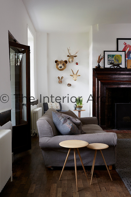 A living room with a large sofa and animal heads on the wall, next to a large fireplace.