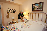 Barbara Bachman, a volunteer docent with the Bonita Springs Historical Society, in the 1930s period bedroom, on exhibit at the Liles Hotel, Bonita Springs, Florida, USA, Dec. 22, 2011. Photo by Debi Pittman Wilkey.