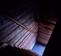 A glimpse of daylight at the bottom of the steep staircase in the corner of this dark barn