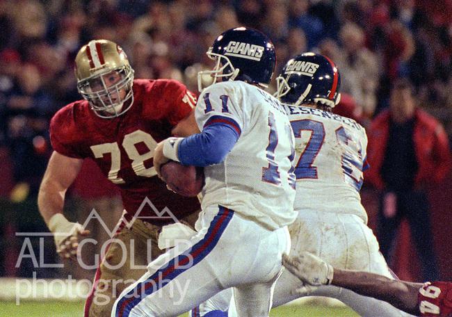 San Francisco 49ers vs New York Giants at Candlestick Park Monday, November 27, 1989..49ers Beat Giants 34-24.49er defensive end Pierce Holt (78) rushes Giants quarterback Phil Simms (11)..