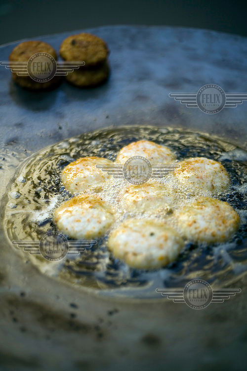 Potato cakes frying in oil on a griddle in Old Delhi.