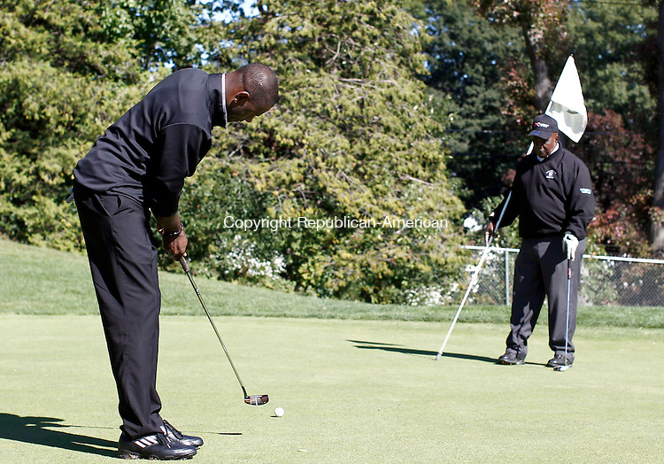 Waterbury, CT- 23 September 2013-092313CM01-  Kevon Bent, of New Haven puts on the 18th green as John Stenson, of New Opportunities Inc. holds the pin at the Country Club of Waterbury Monday afternoon.  The pair were participating in the  19th annual Bobby Bonds Memorial Scholarship Golf Tournament, which is sponsored by New Opportunities Inc.  97 golfers took part in the annual event, which provides scholarships to Waterbury youth who are residents or attend school in the City.  800,000 dollars has been raised since the tournaments inception, said Francine Nido, tournament coordinator.  Christopher Massa Republican-American
