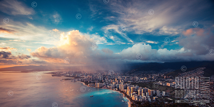 At sunset, a rain cloud over Honolulu casts a glow in the ocean in front of Waikiki, O'ahu.