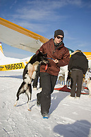 Dropped dog handler Morgan Peters takes a dropped dog from an airplane Thursday to a place to rest in McGrath