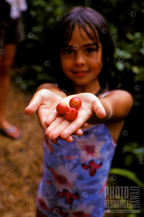 Young local girl in bathing suit holding wild berry
