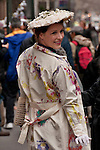 A woman wears a flowered trench coat and white flowered hat to the Easter Parade in New York City on Fifth Avenue