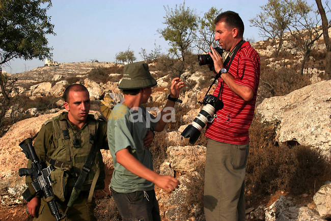 Jewish settler scuffle with Palestinian photographer outside a wooden structure built to mark the end of a 10-month ban on settlement construction, on September 26, 2010, near the Israeli settlement of Kiryat Arba outside the West Bank town of Hebron. Photo by Mamoun Wazwaz