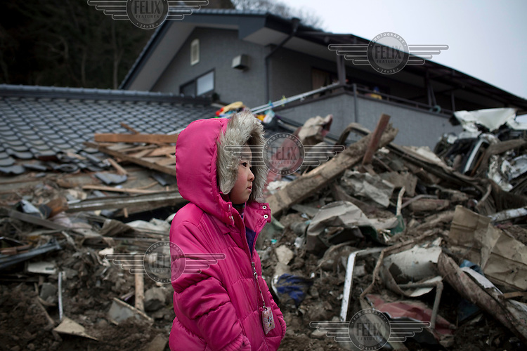 A girl looks at her destroyed house. Thousands of people died in this small town which ran out of body bags. On 11 March 2011 a magnitude 9 earthquake struck 130 km off the coast of Northern Japan causing a massive Tsunami that swept across the coast of Northern Honshu. The earthquake and tsunami caused extensive damage and loss of life.