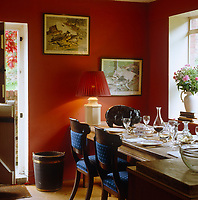 The table in this red country dining room is laid for an intimate meal graced with a marble pig by Michael Cooper
