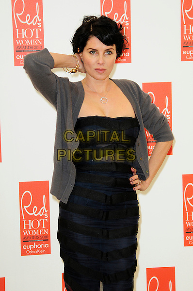 SADIE FROST .attends Red magazine's 'Red Hot Women Awards' at the Saatchi Gallery, London, England, UK, .November 30th 2010..half length hand on hip black dress grey gray cardigan silver necklace touching neck .CAP/CAS.©Bob Cass/Capital Pictures.