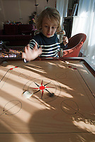 Little blond girl playing Carrom, the Indian board game, France.