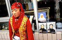 CHINA. Beijing. A woman sells traditonal Islamic dress during the festival of Eid-al-Fitr, marking the end of Ramadan. 2005