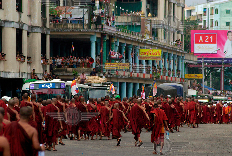 Bystanders line the streets to show their solidarity with protesting Buddhist monks calling for the overthrow of the country's military junta. Having been dispersed by the army firing warning shots, these monks file back to their monasteries. Thousands had taken to the streets again despite a new threat that the military would shoot on sight any gatherings of over four people.