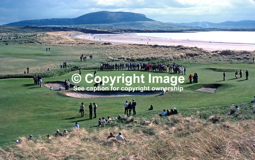 West of Ireland Amateur Open Golf Championship at the spectacular County Sligo Golf Club coastal course at Rosses Point, Co Sligo. Spectators watch a match on the 13th green with a beach and Knocknareay Mountain in the distance. 19820600107c..Copyright Image from Victor Patterson, 54 Dorchester Park, Belfast, UK, BT9 6RJ.  Tel: +44 28 90661296  Mobile: +44 7802 353836.Email: victorpatterson@me.com Email: victorpatterson@gmail.com..For my Terms and Conditions of Use go to http://www.victorpatterson.com/ and click on Terms & Conditions