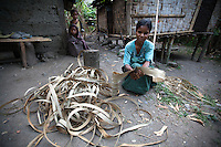 A woman uses the skin from a particular kind of local tree to weave ropes, which farmers will later use to look after their animals in the mountain town of Laclubar, Timor-Leste on Wednesday, Oct. 19th, 2011.  Photographer: Daniel J. Groshong/The Hummingfish Foundation