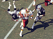 Washington Redskins running back George Rogers (38) carries the ball during the game against the Los Angeles Raiders at RFK Stadium in Washington, D.C. on September 14, 1986.  Raiders players in pursuit are left outside linebacker Jerry Robinson (57) and free safety Vann McElroy (26).<br /> Credit: Arnold Sachs / CNP