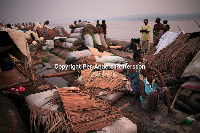 MBANDAKA, DEMOCRATIC REPUBLIC OF CONGO JULY 1: Alice Mboyo (r), age 18, passes time with her mother, Mekutuala, age 44, while traveling on a boat made of big trees on the Congo River on July 1, 2006 outside Mbandaka, Congo, DRC. The boat traveled with about 150 passengers from Bumba to Kinshasa, a journey of about 1300 kilometers. Alice traveled with her 10-month old baby, mother and two younger sisters from Bumba to the capital Kinshasa. The Congo River is a lifeline for millions of people, who depend on it for transport and trade. Passengers slept in the open, with their goats, pigs and other animals. Boat travel is the only option for most people along the river as there?s no roads or infrastructure. Very few can afford to fly in a plane to the capital Kinshasa. During the Mobuto era, big boats run by the state company ONATRA dominated the river. These boats had cabins and restaurants etc. All the boats are now private and are mainly barges that transport goods. The crews sell tickets to passengers who travel in very bad conditions. The conditions on the boats often resemble conditions in a refugee camp. Congo is planning to hold general elections by July 2006, the first democratic elections in forty years. The Congolese and the international community are hoping that Congo will finally have piece and the country will be rebuilt..(Photo by Per-Anders Pettersson/Getty Images)..