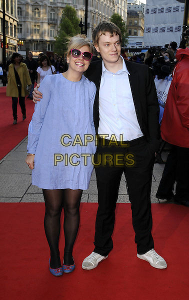"LILY ALLEN & ALFIE ALLEN.World Premiere of ""Flashbacks of a Fool"" at the Empire, Leicester Square, London, England..April 13th 2008.full length blue dress dyed blonde hair pink sunglasses shades tights black suit white trainers brother sister siblings family Chanel logo red shoes gingham arm over shoulder .CAP/CAN.©Can Nguyen/Capital Pictures"