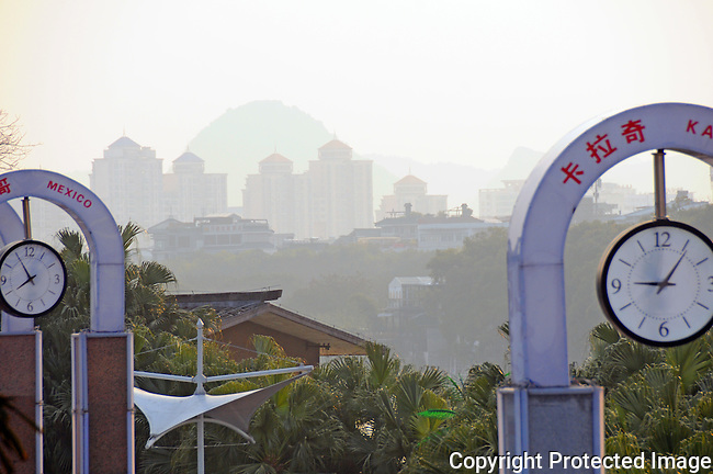 clock towers of many nations along  the Li River, with the hazy outline of Guilin buildings and hills in background