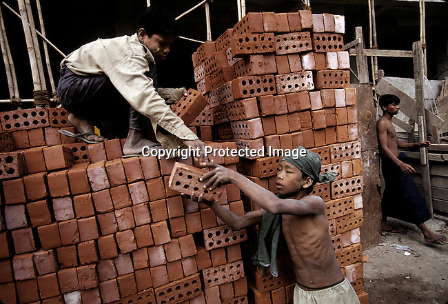 Boys carrying bricks at construction site on December 24, 1996 in central Rangoon (Yangon), Burma. A military government took control after they annulled democratic elections in 1988 and many opposition people are in prison. (Photo by: Per-Anders Pettersson)