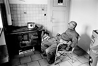 Switzerland. Canton Graubunden. Viano. Poschiavo valley. Luigi Merlo seats and rests in the kitchen of his small farm. Wood stove. Swiss alpine farmers. Alps mountains peasants.  © 1995 Didier Ruef