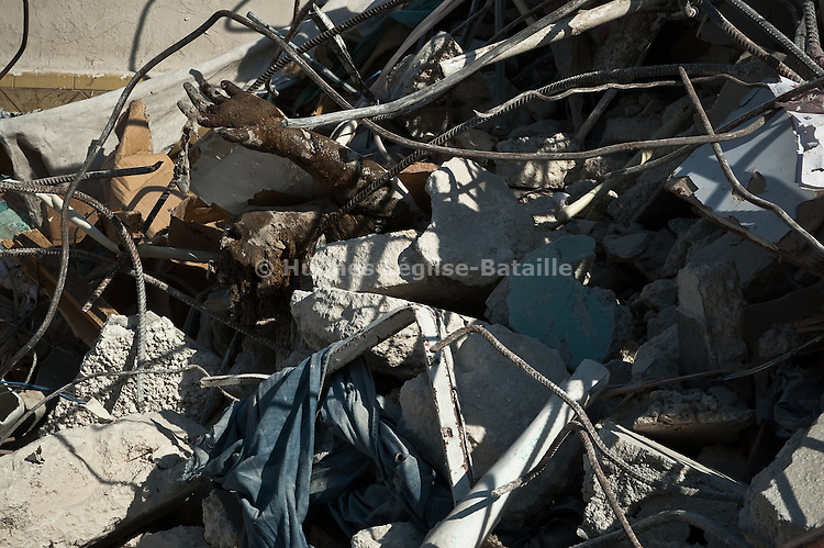 Un corps émerge encore des décombres d'une maison sur Grand Rue à Port-au-Prince le 22/01/2010, 10 jours après le séisme.
