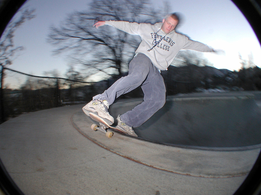 Skateboarder Nate Furr pulls a boardslide in the dead of winter at the skatepark in Durango, Colorado in 2002, seen through a fisheye lens.