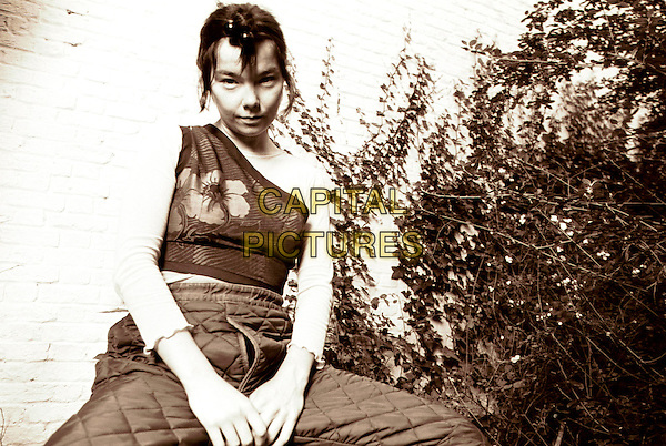 BJORK.Photo Session.Ref:Ian Jennings.3/4 length black white sepia seated sitting off the shoulder top patchwork trousers unusual hair style bobbles.www.capitalpictures.com.sales@capitalpictures.com.©Capital Pictures...
