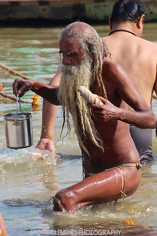 An elderly man leaves the holy waters at Prayag after his bath, believed to wash away all his sins, carrying a can of water and his freshly washed lunghi.