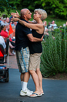 A couple dances off the side of the stage at an outdoor concert at the ampitheater in Alum Creek Park in Westerville as part of a summer concert series.