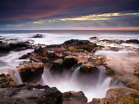 A blowhole along the Big Island's Keahole Point coastline at sunset.