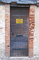 An old wooden door on a stone house in the old town, sign saying Federation des Vins du Bergeracois, the office of the federation of the wines of Bergerac Dordogne France
