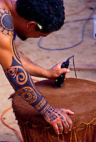 A tattooed Hawaiian man shaves the head of a newly made pahu (drum).