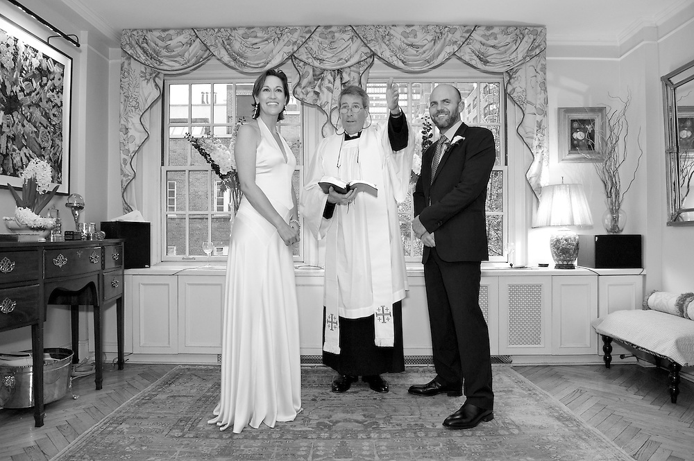 Black & white shot of ceremony-  bride and groom standing with priest.