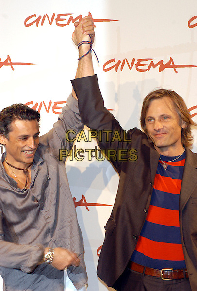 "ENRICO LO VERSO & VIGGO MORTENSEN.Photocall for ""Alatriste"" at the Rome Film Festival, Rome, Italy..October 16th, 2006.Ref: CAV.half length arms in air blue red striped stripes top gray grey shirt jacket.www.capitalpictures.com.sales@capitalpictures.com.©Luca Cavallari/Capital Pictures."