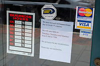 """A sign at Sun-Rite Dry Cleaners reads """"We have reduced our business hours due to COVID-19 concerns"""" in the Belmont Center shopping district in Belmont, Massachusetts, on Fri., March 20, 2020. Many shops around the region have closed or greatly reduced hours as part of social distancing efforts in response to the growing coronavirus COVID-19 global pandemic."""