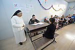 Sister Anahid, a member of the Dominican Sisters of St. Catherine of Siena, observes the examination of a student in a primary school she supervises in Dohuk, Iraq. Most of the students were displaced from their home villages when the Islamic State group took over portions of the Nineveh Plains in 2014. Because they came from communities with Arabic curriculum schools, they often don't fit well in schools in the villages where they resettled, because those schools teach in Kurdish or Assyrian. So the religious order started the school, which has students from several faiths, including Islam and Christianity. The Christian Aid Program Nohadra - Iraq (CAPNI) provides transportation for many students to Dohuk from the rural villages where their families have taken refuge.