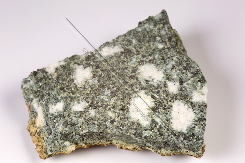 This is a sample of the rock used to make the monument Stonehenge in England.; This is a sample of Preseli Spotted Dolerite—a chemically altered igneous rock containing spots or clusters of plagioclase feldspar. It is a medium grained dark and heavy rock; harder than granite.; The bluestones at Stonehenge were placed there during the third phase of construction at Stonehenge around 2300 BC.; The majority of them are believed to have been brought from the Preseli Hills; about 250 miles away in Wales.
