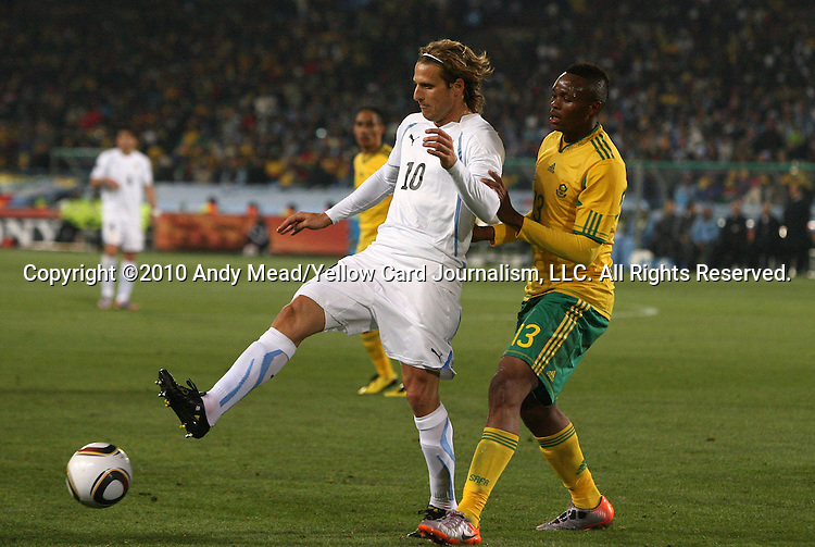 16 JUN 2010: Diego Forlan (URU) (10) and Kagisho Dikgacoi (RSA) (13). The South Africa National Team lost 0-3 to the Uruguay National Team at Loftus Versfeld Stadium in Tshwane/Pretoria, South Africa in a 2010 FIFA World Cup Group A match.
