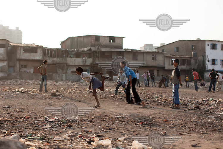 A game of cricket on a patch of wasteland in Dharavi slum.