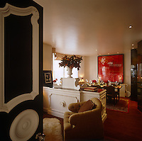 A large contemporary artwork hangs behind the table in the dining room